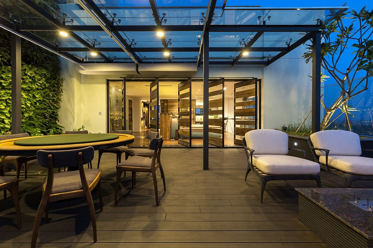 Glass and steel pergola offers shade to the outdoor dining and lounge