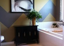Gray and yellow chevron stripes create a a stylish accent wall in the bathroom