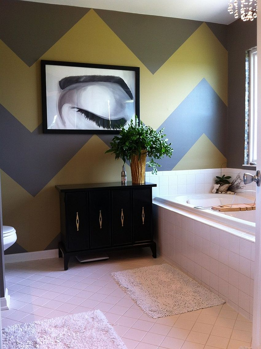 Gray and yellow chevron stripes create a a stylish accent wall in the bathroom [Design: Home Girl Décor]