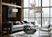 Grey sofa and wooden walls in a chalet styled by CB2