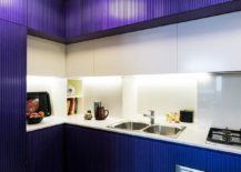 Lighting enlivens the small kitchen in dark blue and white