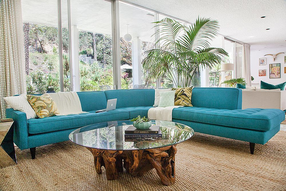 Midcentury family room with striking couch in turquoise and a cool coffee table [Design: Apt2B / HOMEPOLISH]