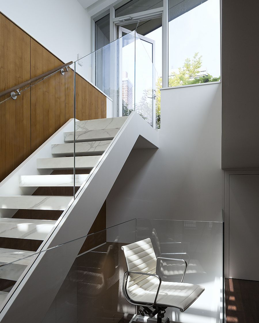 Open glass and marble stairs connect the various levels of the new and improved triplex