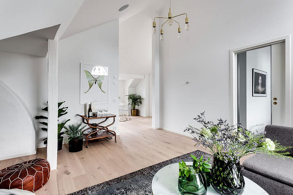 Pops of green and a bright ottoman provide color to the Scandinavian style apartment in Stockholm