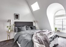 Tiny white bedroom with gray bed and large windows