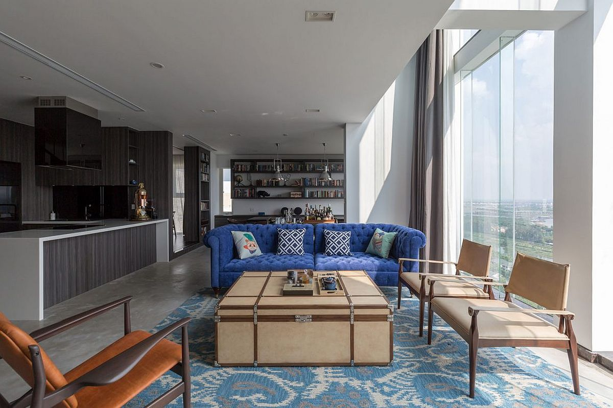View of the living area, kitchen and dining room at modern green penthouse