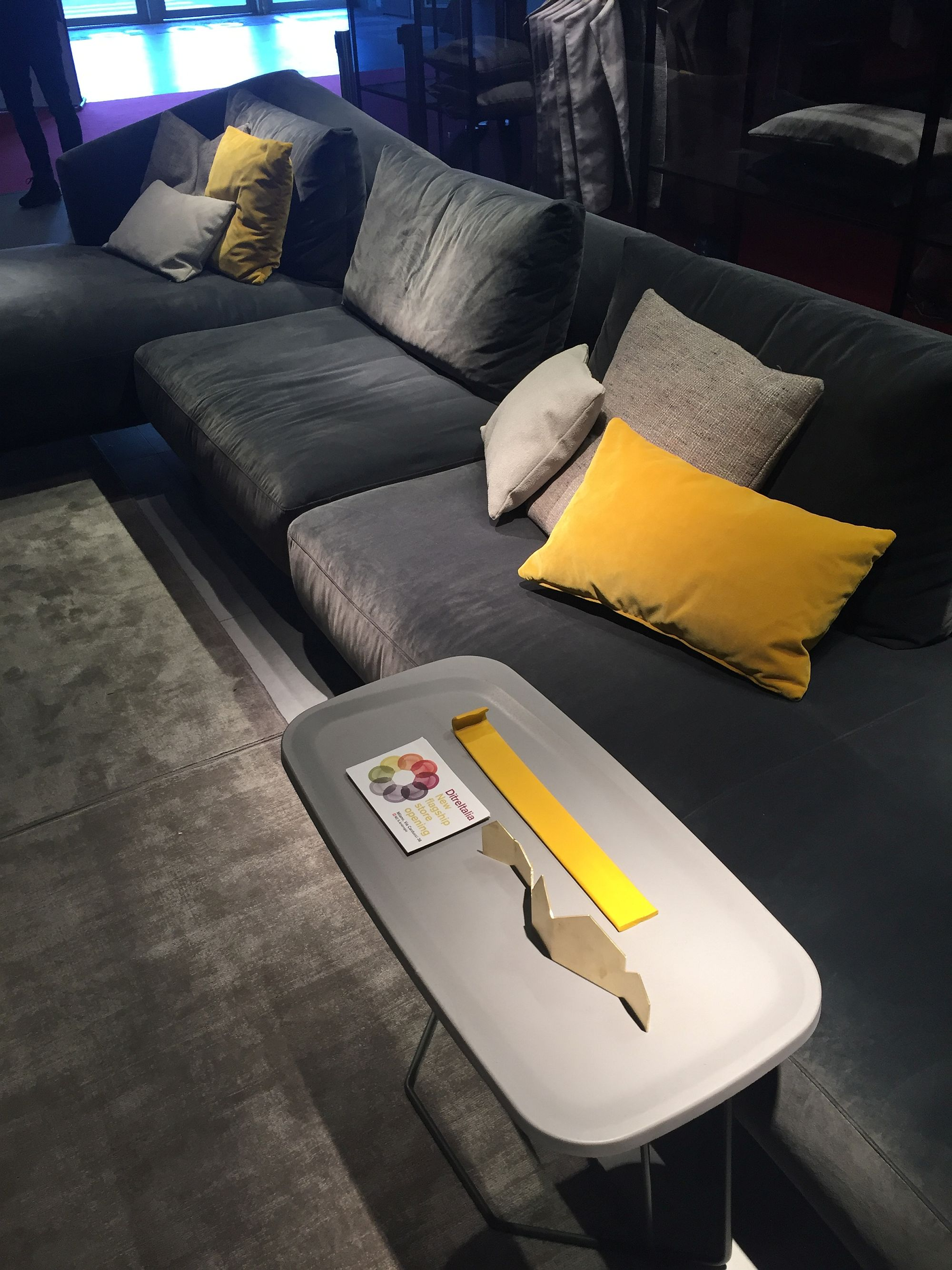 A dash of yellow using accent pillows brings color to the gray living room couch
