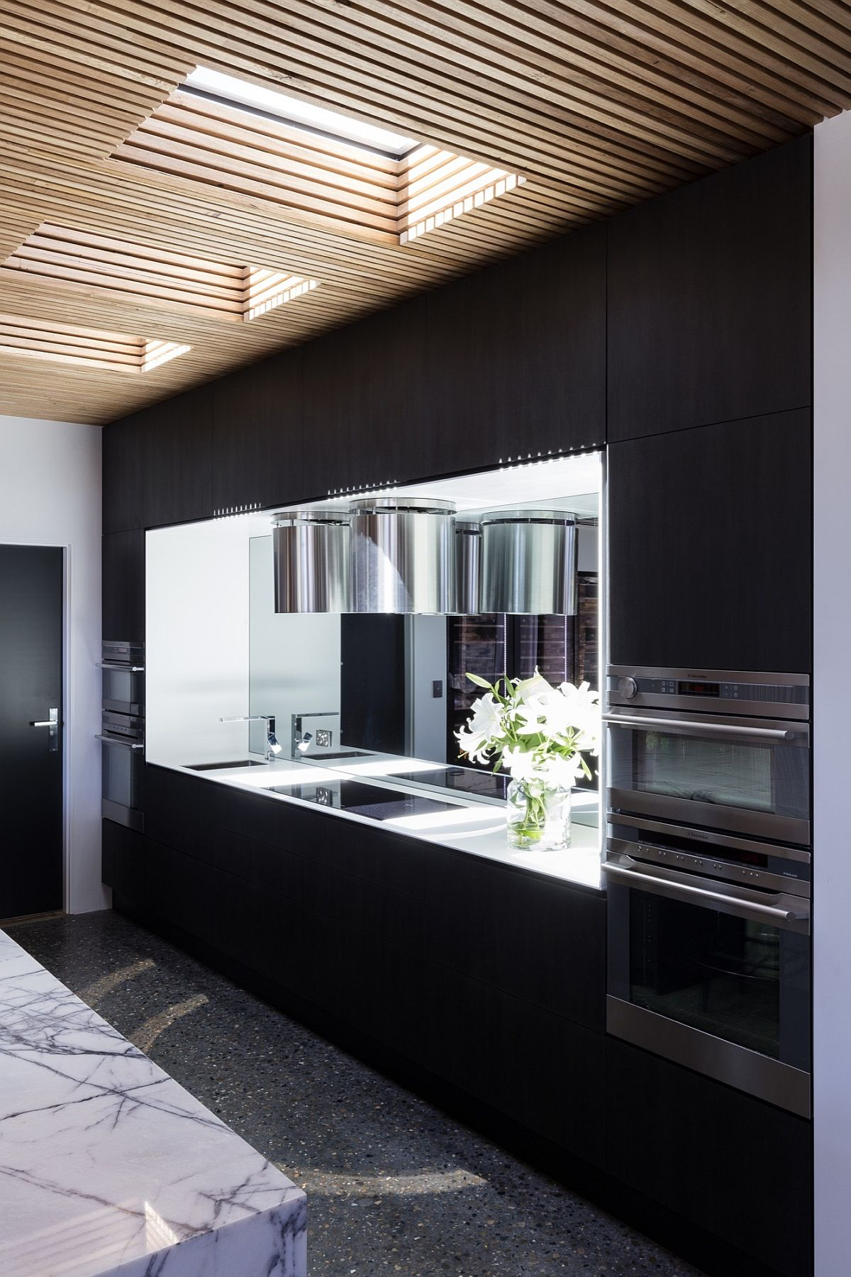 Black kitchen cabinets and white marble island present a contrasting picture