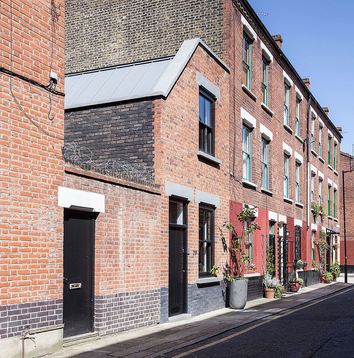 Classic brick exterior of the revamped home in London Congested Upholsterer's Workshop in London Altered into Multi Level Modern Home