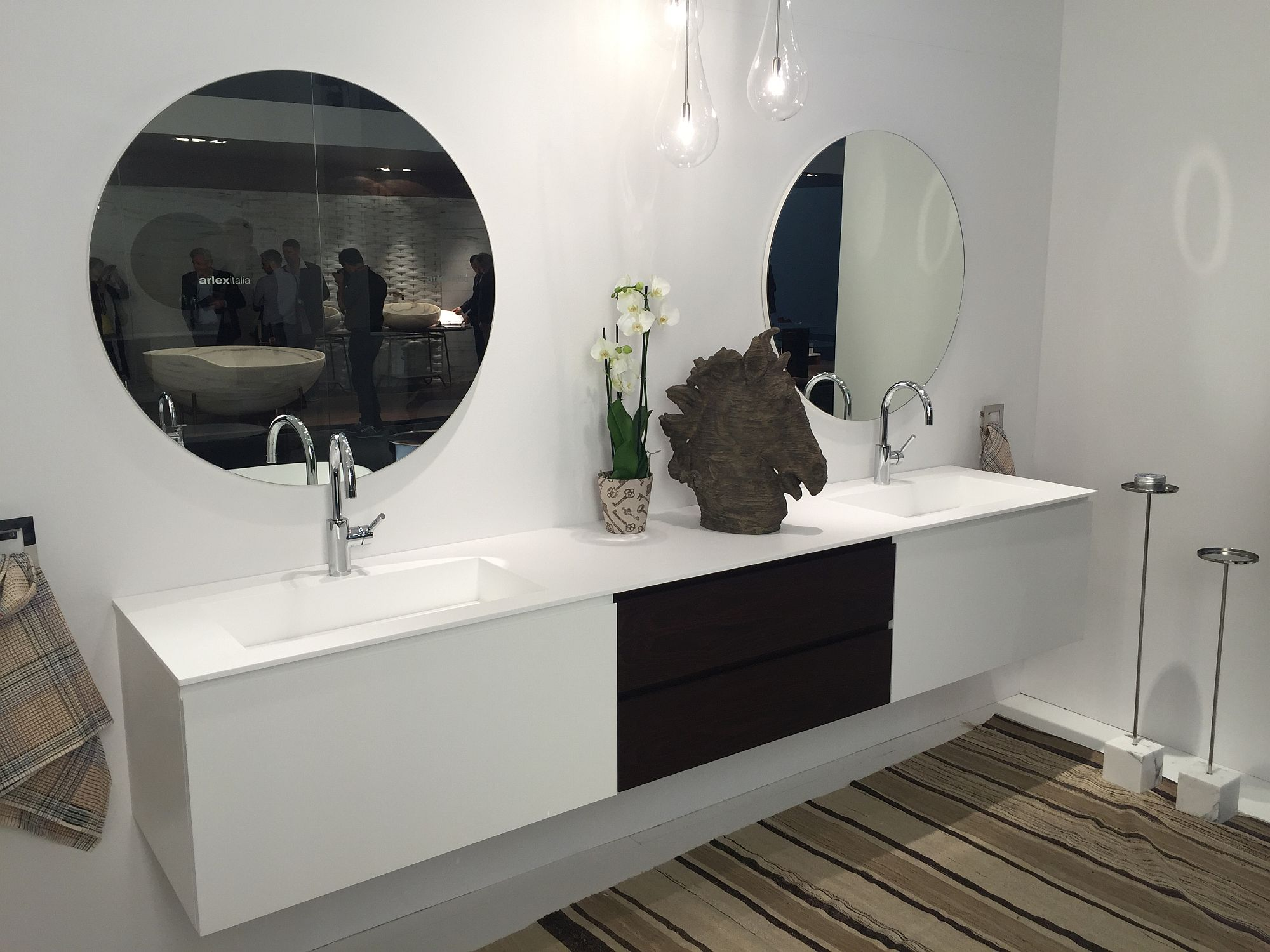 Contemporary bathroom vanity in white with a small vase and flowers that bring color to the setting