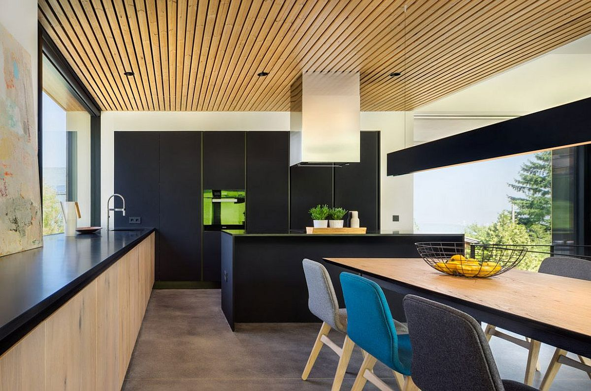 Contemporary kitchen in black and wood along with smart dining