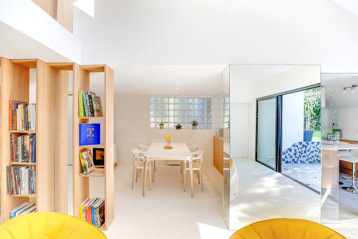 Dining room and kitchen concealed behind the glass pillar and the bookshelves