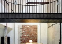 Dining room with exposed brick wall backdrop and a metallic bridge above