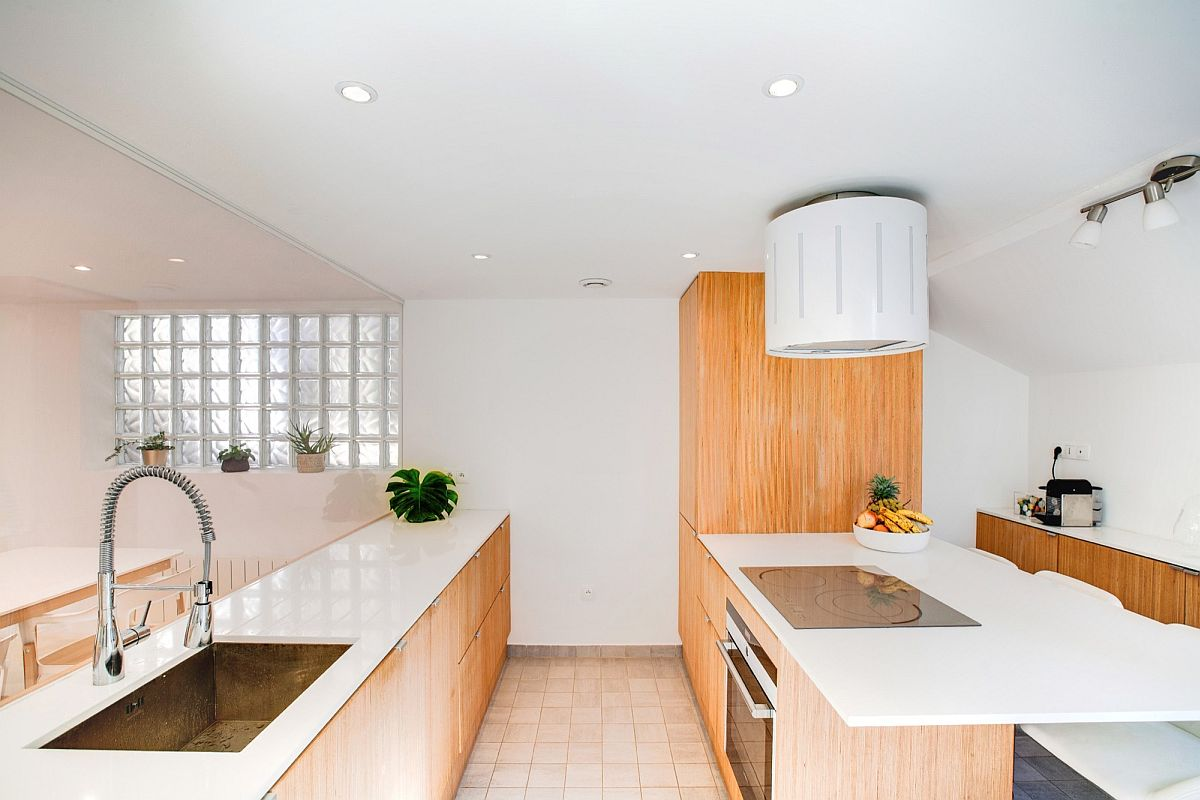 Glass doors and walls seperate the kitchen from the living area