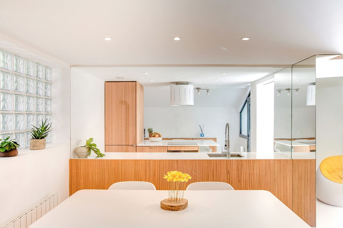 Glass walls between the kitchen and dining area llow light to pass throug