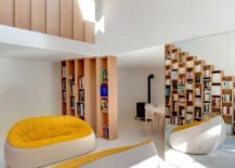Glassy-pillar-draped-in-mirrors-reveals-the-beech-stepped-bookshelf-at-the-entrance-217x155