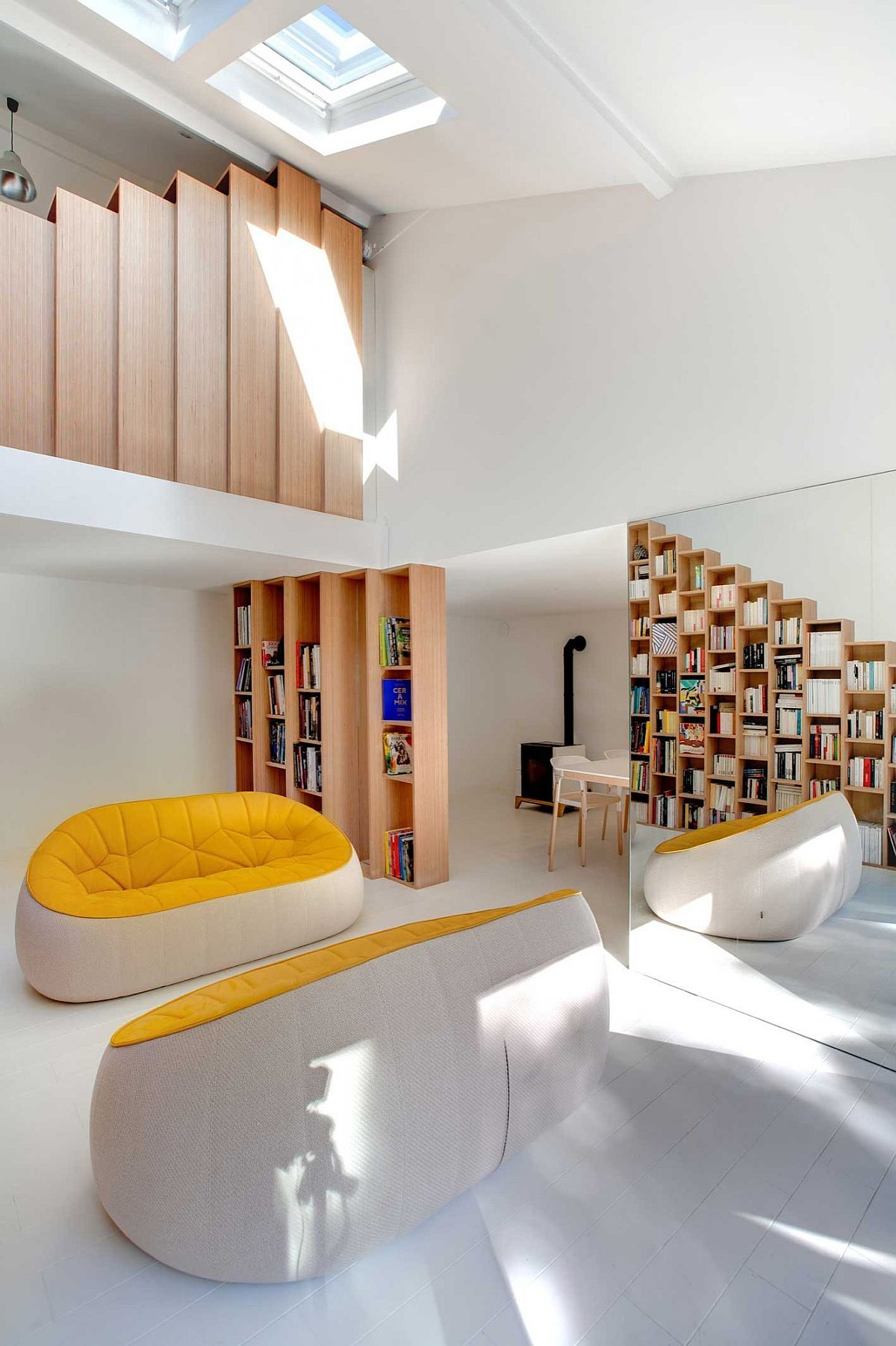Glassy pillar draped in mirrors reveals the beech stepped bookshelf at the entrance