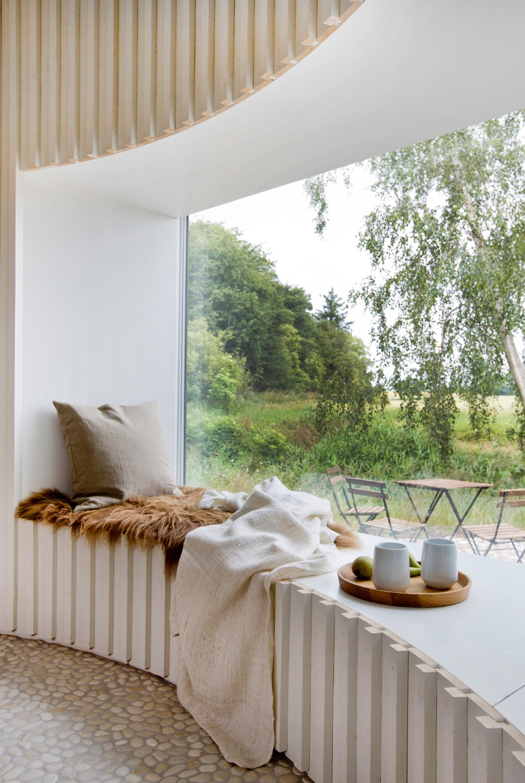 A cosy corner in a Danish holiday home designed by Copenhagen-based architectJan Henrik Jansen. Photo byLene K Fotografi via Dezeen.