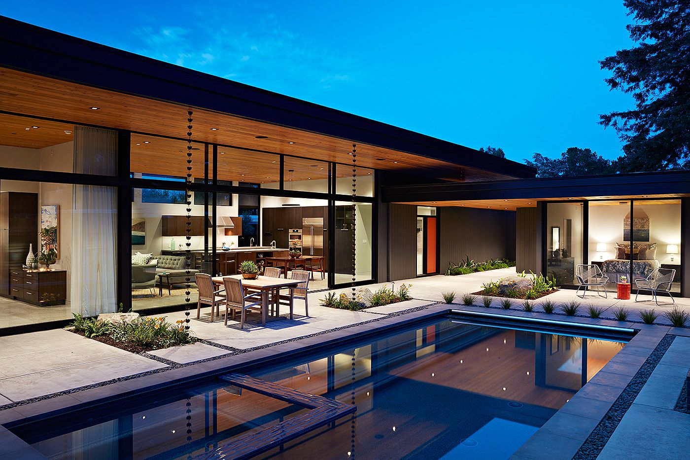 Large glass walls connect the interior with the rear yard and the pool