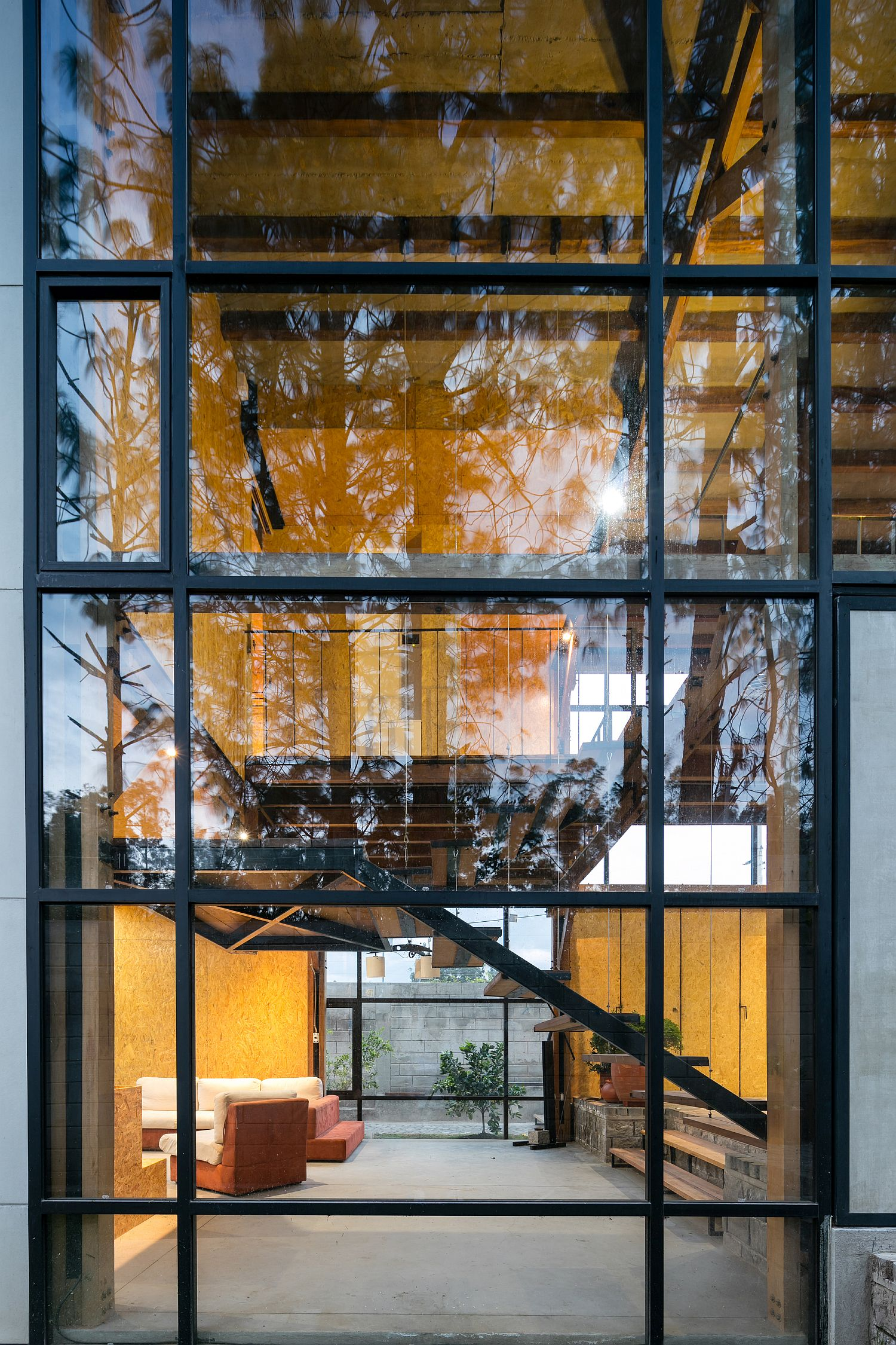 Large glass windows with metallic frame bring the outdoors inside