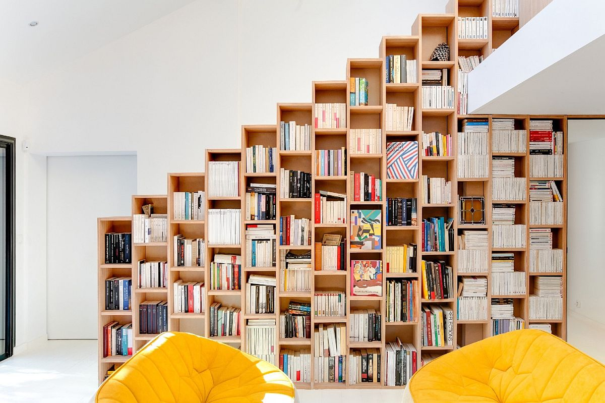 Living room beech bookshelf acts also a stairway railing on the lower level