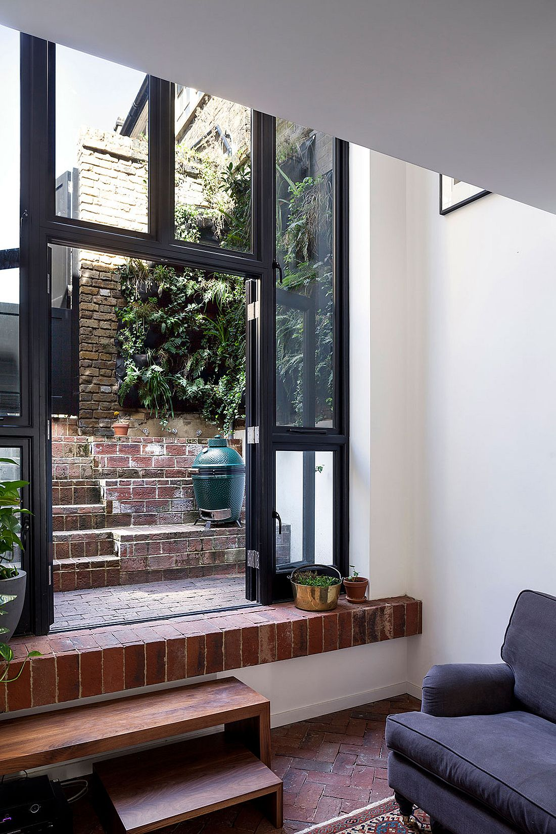 Living room leads into the private rear courtyard of the london home
