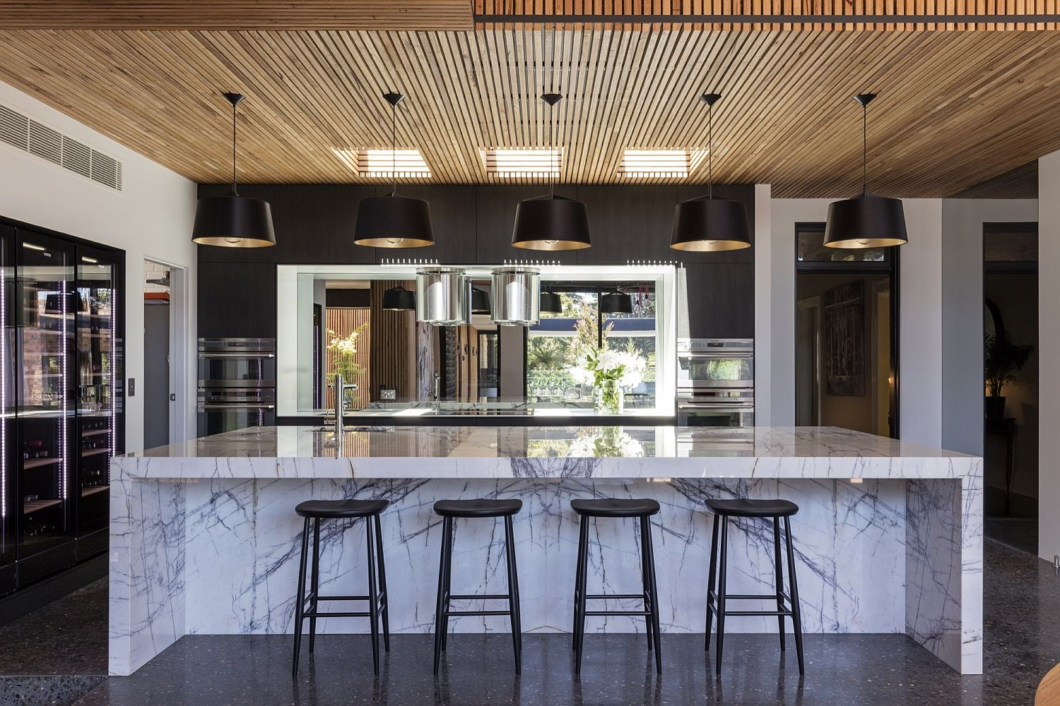 Marble kitchen island with pendant lighting above it