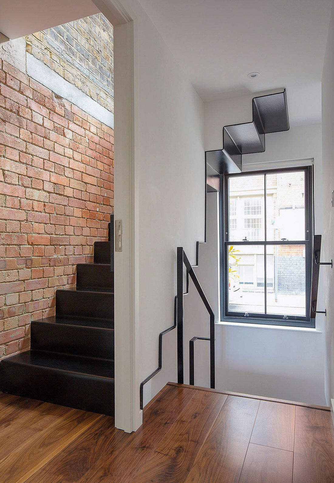 Metallic staircase leads to the master suite on the top level