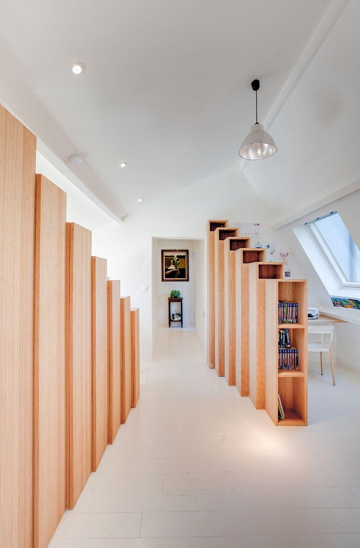 Mezzanine level beech shelving units hide the bedroom entrance