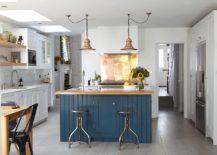 Modern industrial kitchen with a shiny copper backsplash