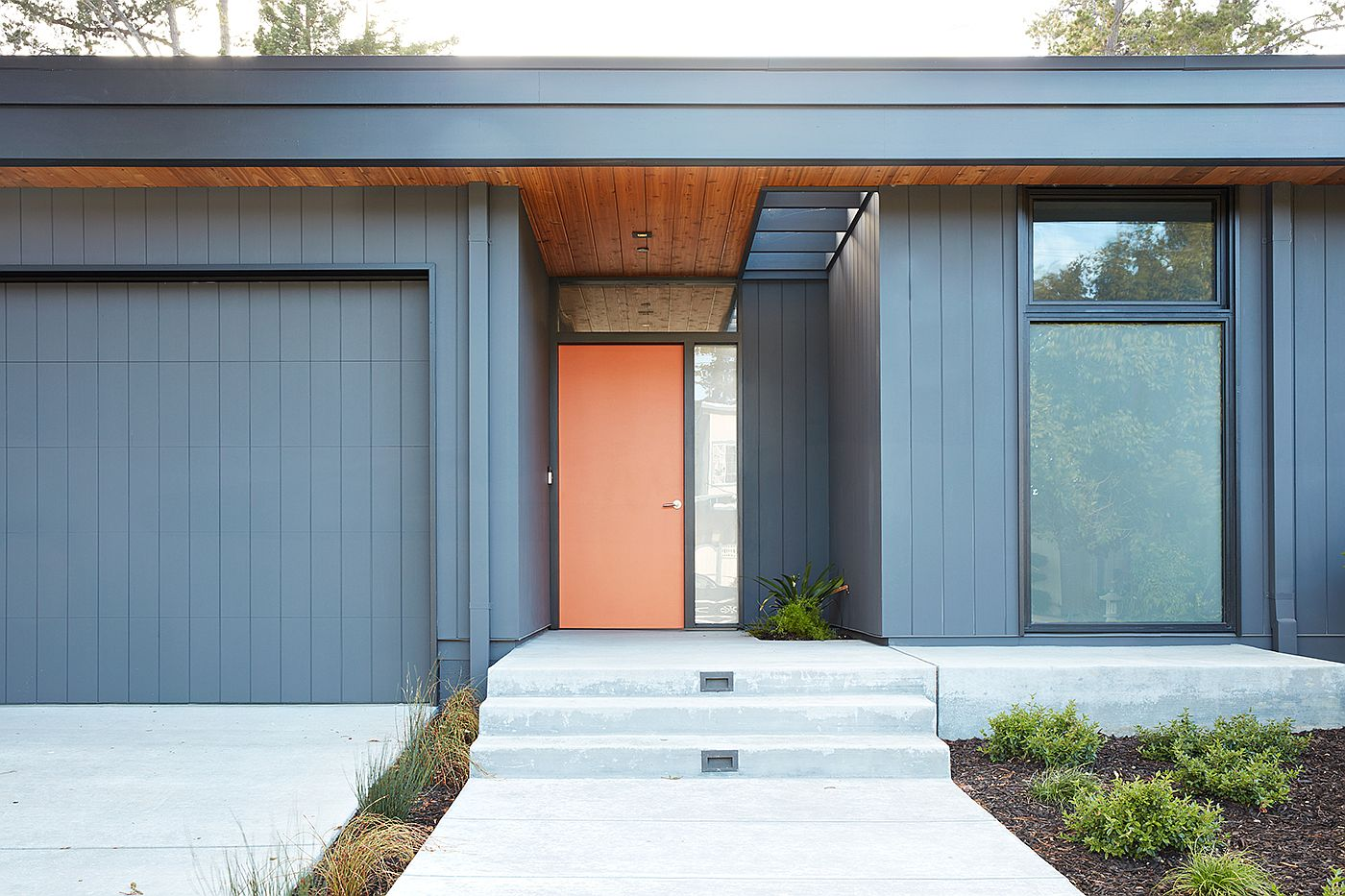 Orange door and gray exterior give the home a classic Eichler-inspired look