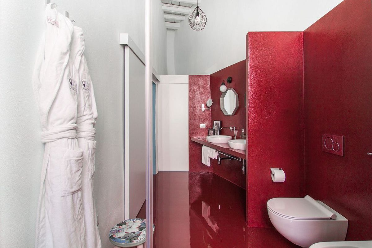 Red floor and walls in the bathroom present contrasting textures