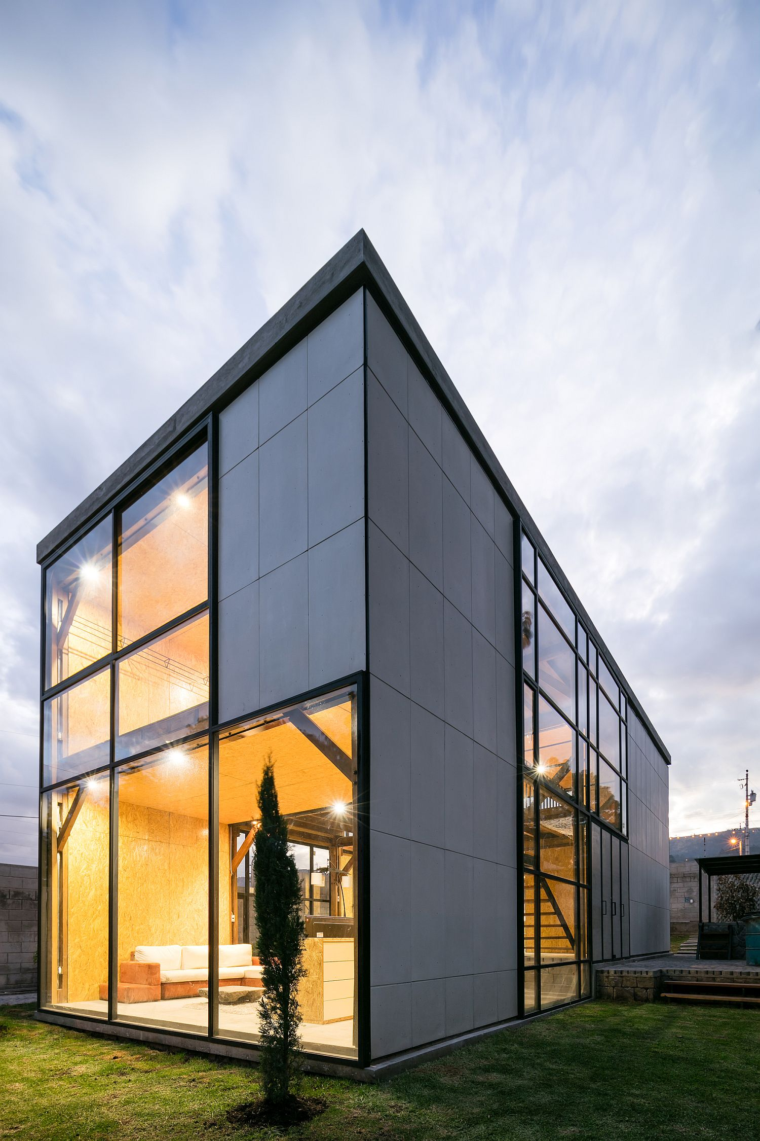 Simple cement panels with socket joints and glass windows shape the multi-generational home in Quito