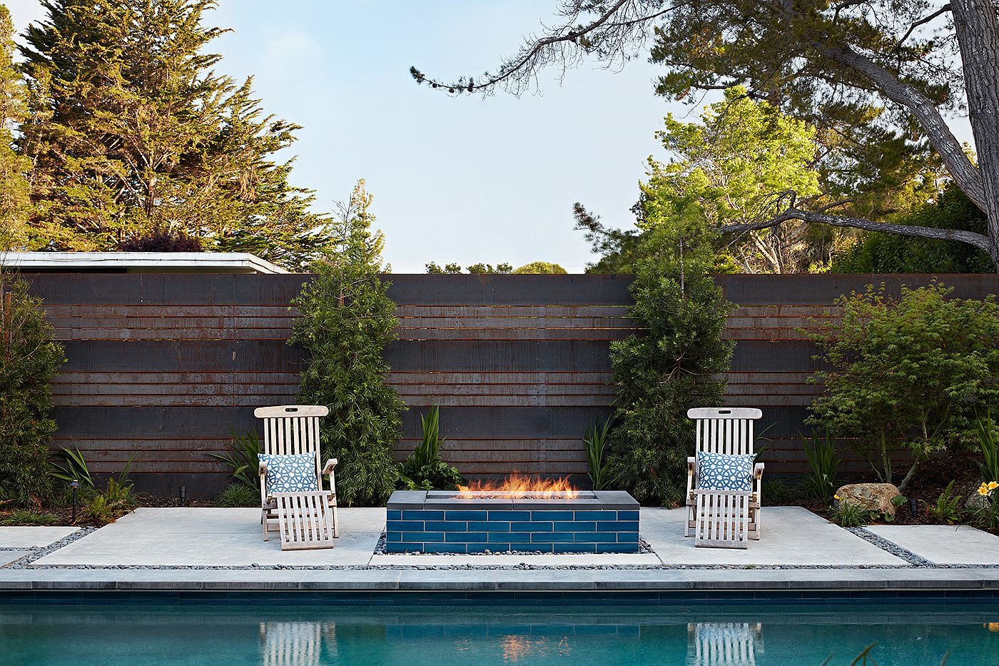 Simple hangout next to the pool with a modern fireplace