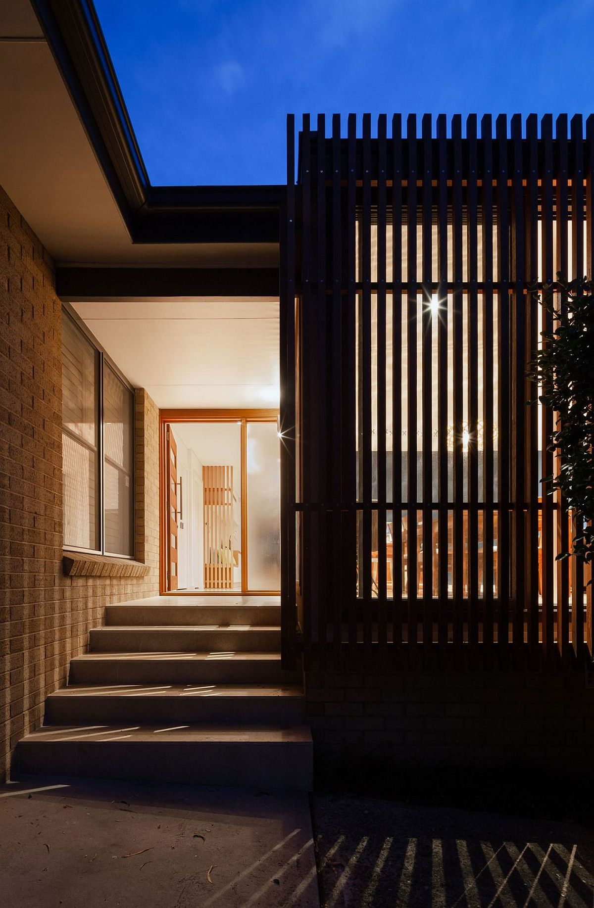Slated timber gives the home a cool visual even after sunset