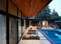 Sliding glass doors and glass walls connect the living area with the landscape and pool outside