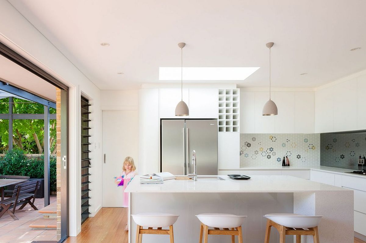 White and wood kitchen with a backsplash that brings pops of color