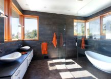 Window frames and towels in orange add a cool, colorful touch to the serene bathroom in gray
