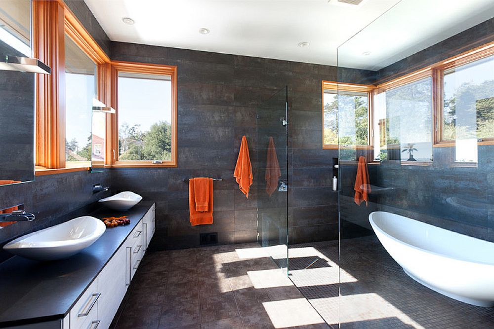 Window frames and towels in orange add a cool, colorful touch to the serene bathroom in gray [Design: Jody Brettkelly]