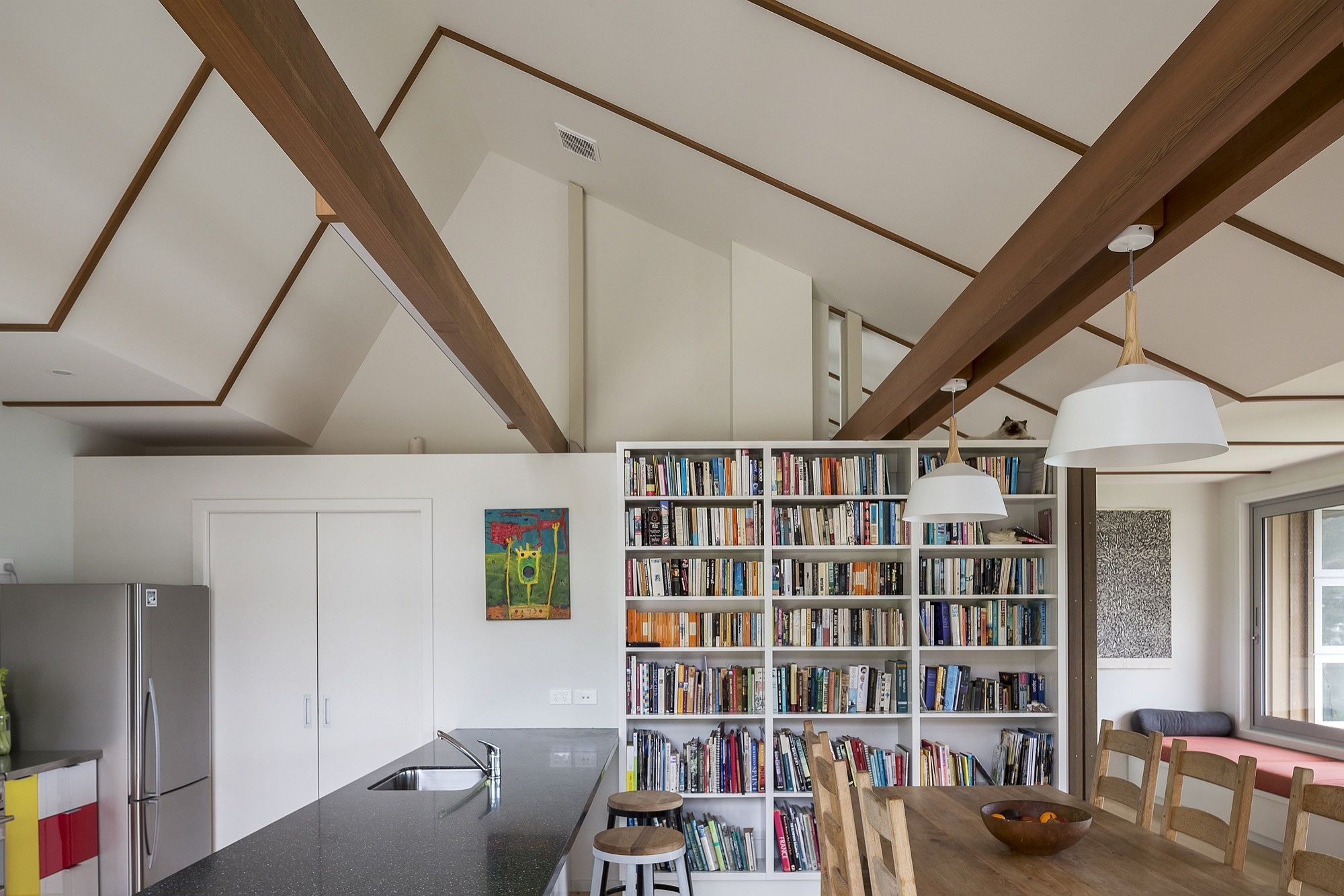 Bookshelf creates a cool backdrop in the modern kitchen