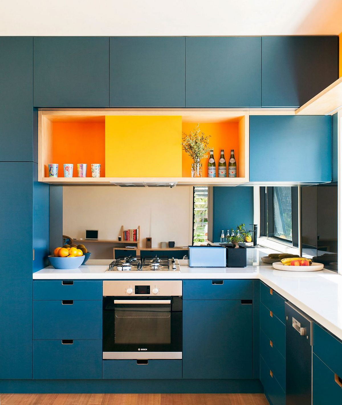Bright blue cabinets and orange bring energy to the modern kitchen