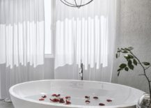 Candles-and-globes-make-a-cool-pendant-above-the-luxurious-bathtub-217x155