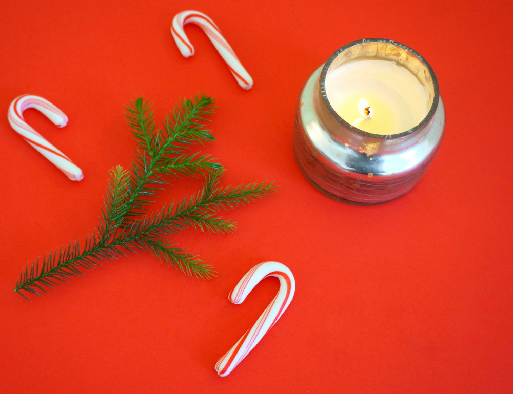 Candy canes greenery and a flickering candle create holiday cheer Making Spirits Bright: Warm, Rejuvenating Holiday Decor