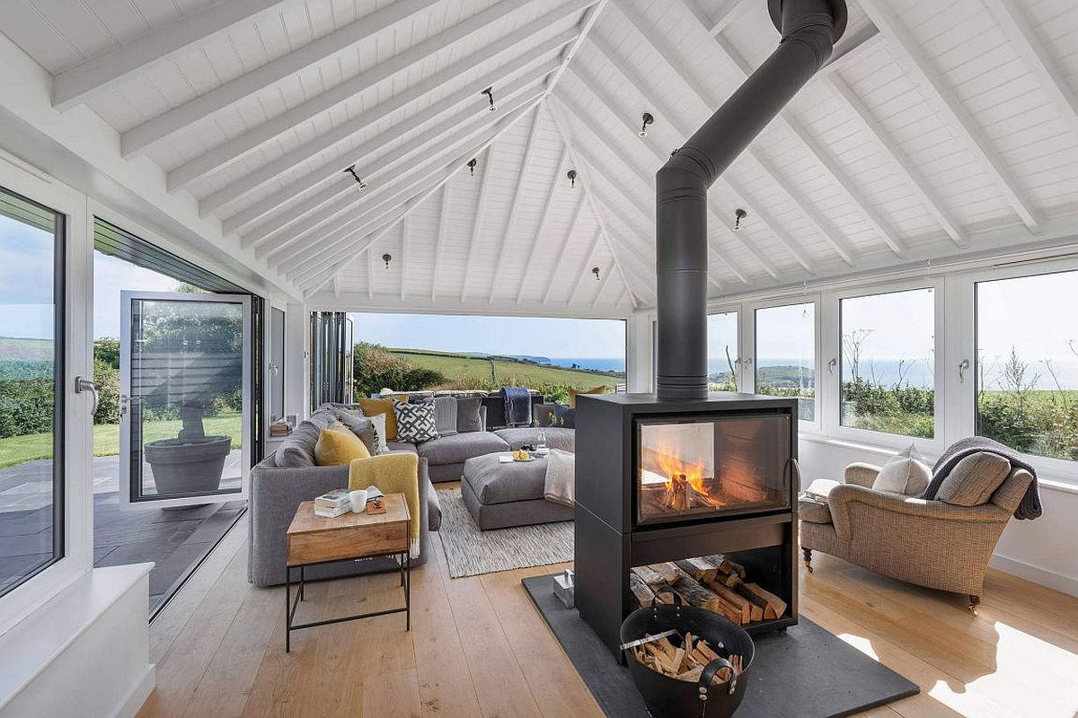 Central double sided fireplace of the coastal home 1960's Bungalow Altered into a Hypnotic Coastal Home with an Amazing View