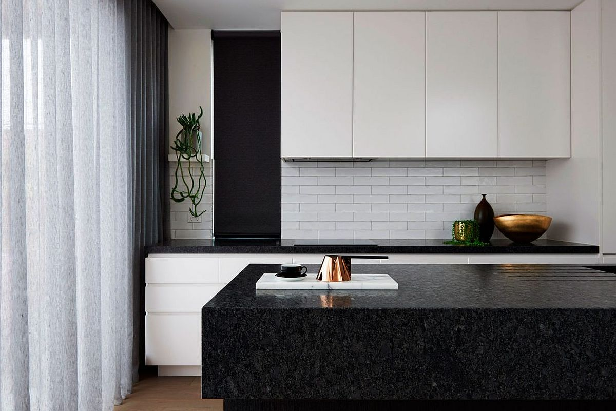 Contemporary kitchen in white with a black stone island