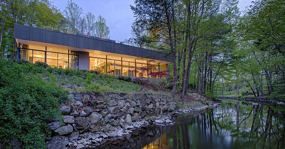 Contemporary lakeside green home with a living roof
