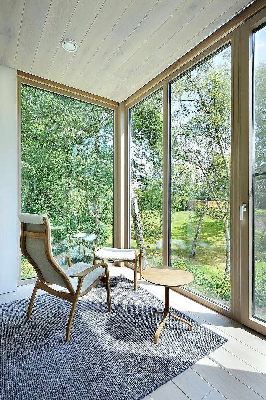 Corner glass walls open up the interior to the forest outside