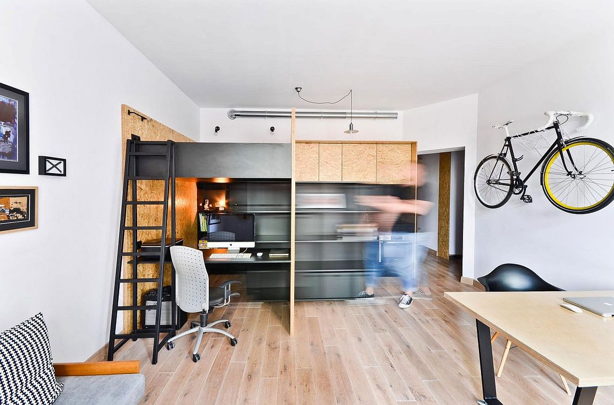 Custom crafted box in the apartment contains workspace loft bed kitchen and storage space Kid Friendly Multifunctional Design Studio and Apartment in Poznan