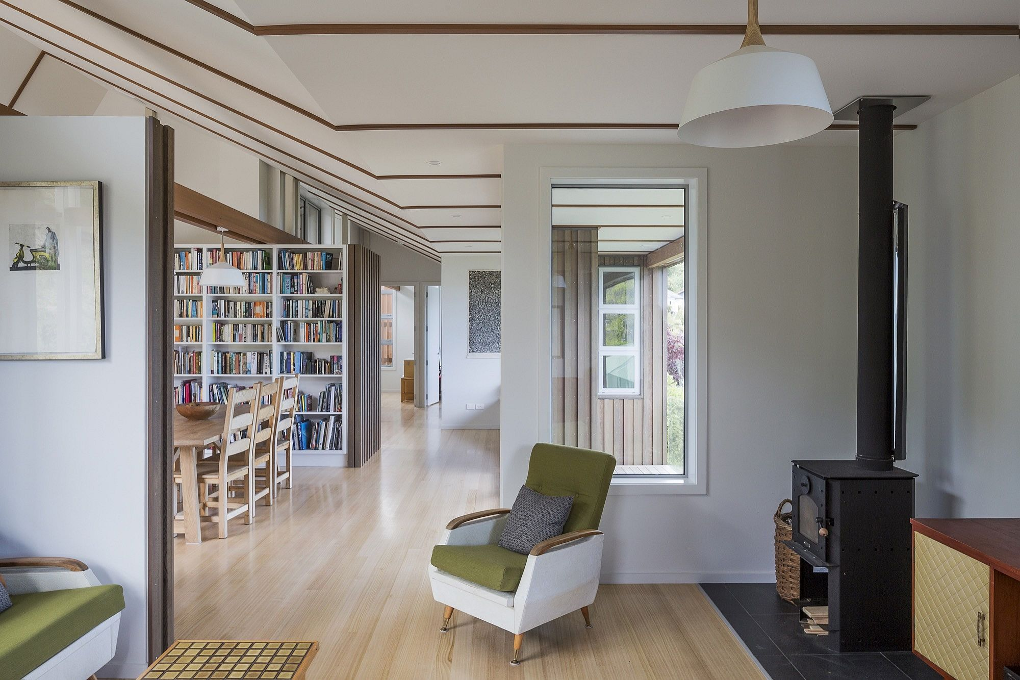 Elegant and neutral interior of the modern home in Christchurch with large bookshelf