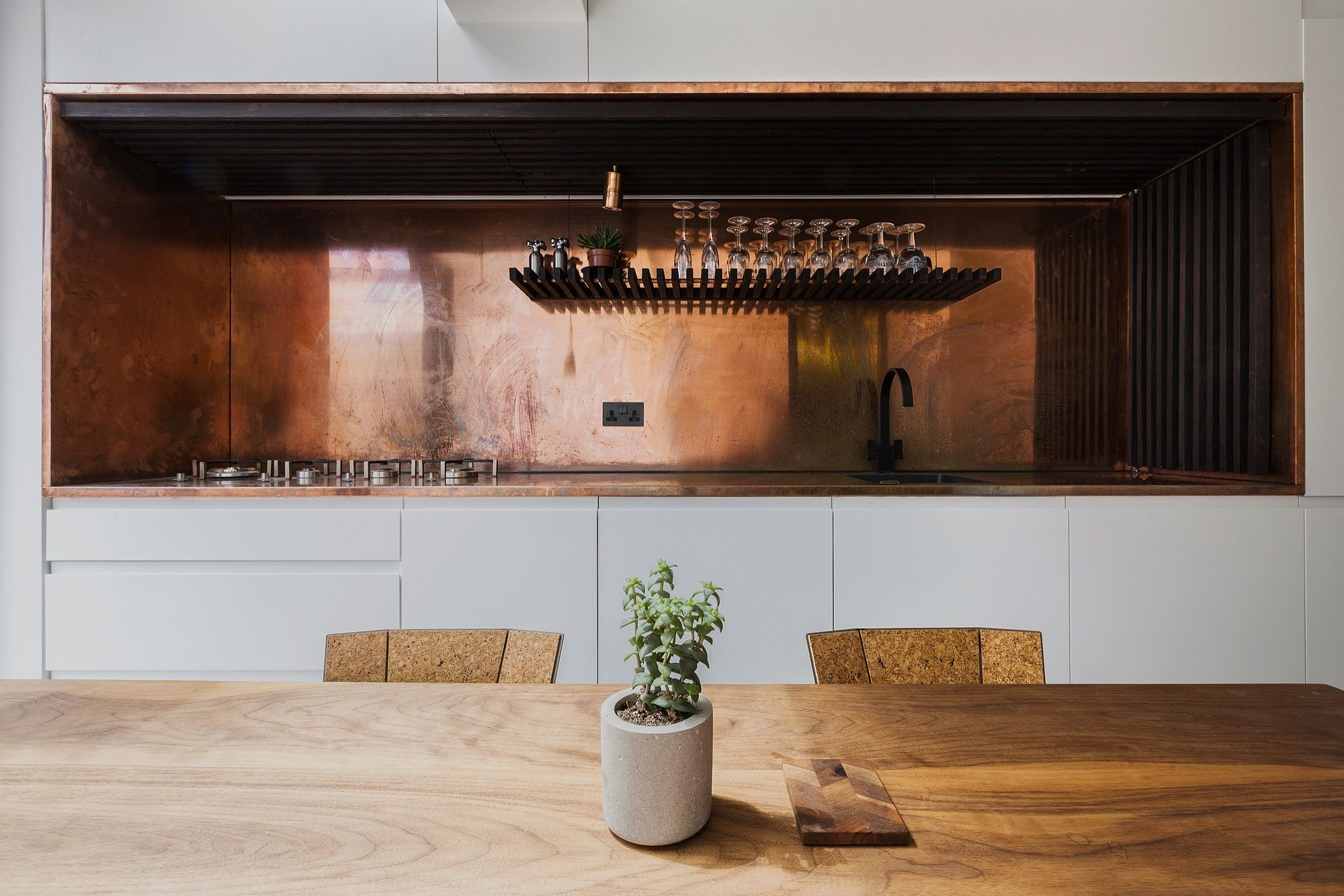 Exquisite kitchen workspace and backsplash in copper along with charred larch slats
